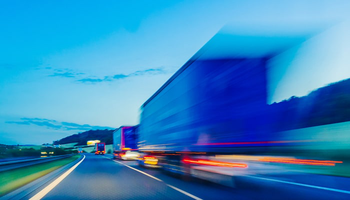 Stock photo of line of trucks on the road at dusk.