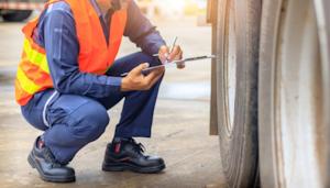 Person conducting a semi-truck tire inspection