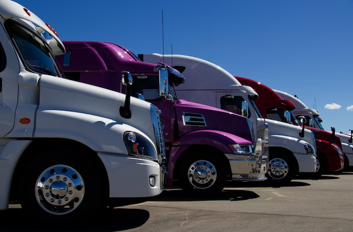 White and purple trucks on lot