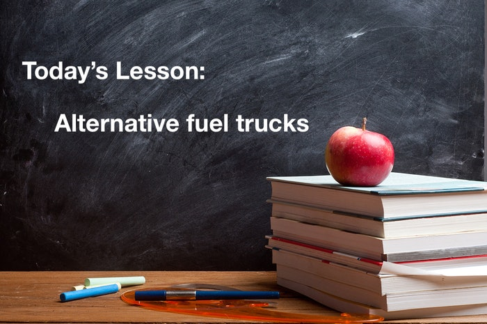 Today's Lesson: Alternative fuel trucks on a chalkboard behind a stack of books with an apple