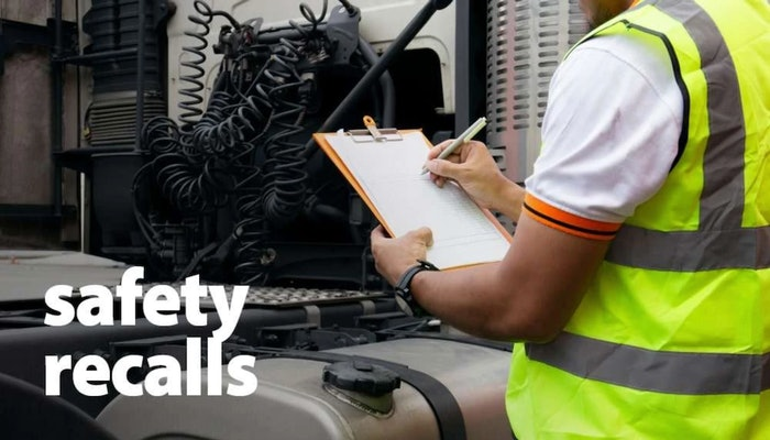 person wearing a safety vest and holding a checklist while inspecting a semi-truck