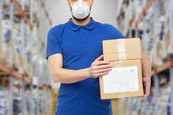Employee wearing mask carrying boxes