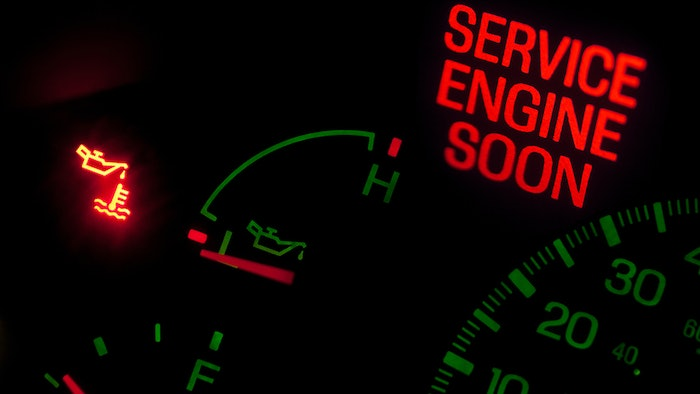 Truck dashboard with Service Engine Soon light.