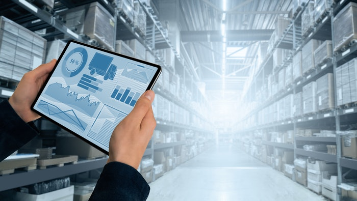 hands holding a tablet with graphs in the of a warehouse